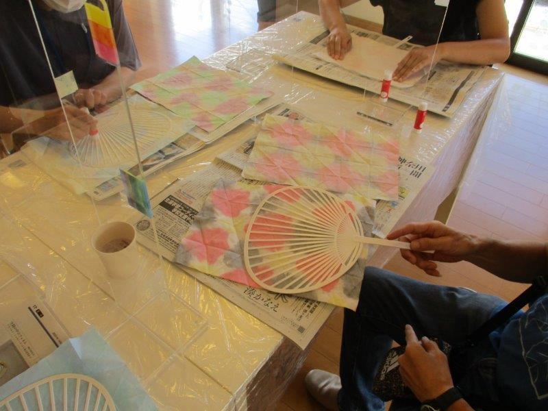 うちわ作り、染めた紙をうちわの骨に貼ります